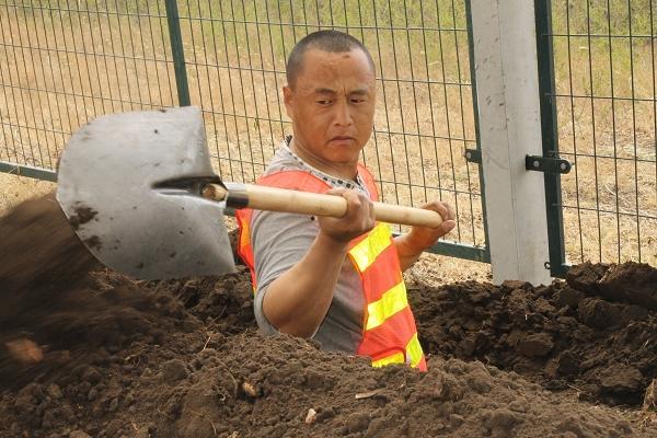 滨州电气化项目部员工进行挖电缆沟作业.JPG