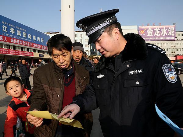 民警为旅客递上宣传单.jpg