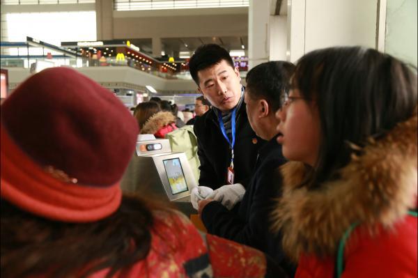 图8为成都车辆段党员突击队员指引乘客实名制验票进站.JPG
