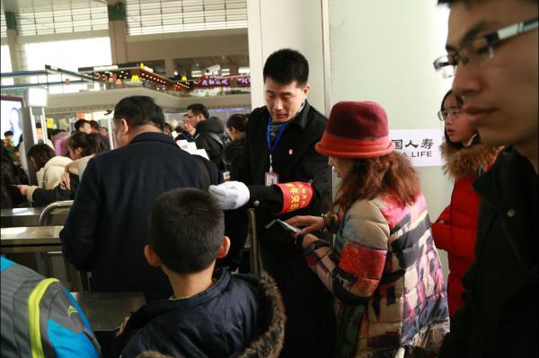 图9成都车辆段党员突击队员指导旅客使用轧机验票.JPG