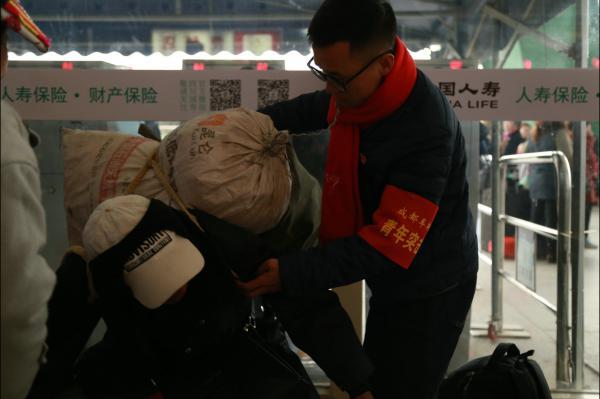 图6成都车辆段青年突击队员帮助旅客整理行李乘车.JPG