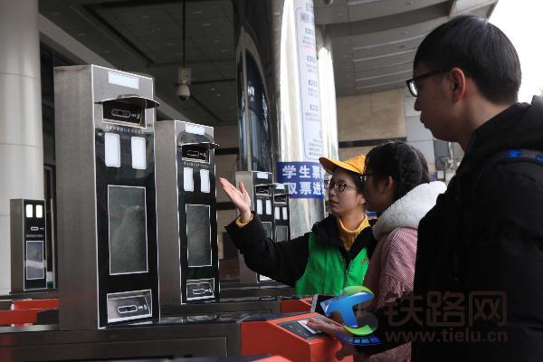 志愿者帮助旅客使用人脸识别系统进站1.jpg