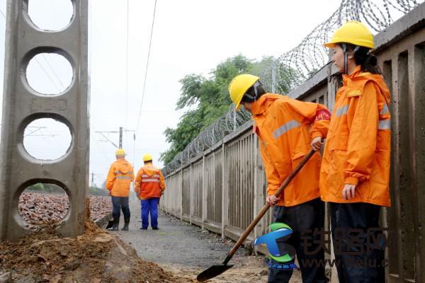 图一为:7月22日,郑州供电段职工雨中巡视接触网供电设备,并对新立供电支柱进行培土加固,确保供电安全稳定。.jpg
