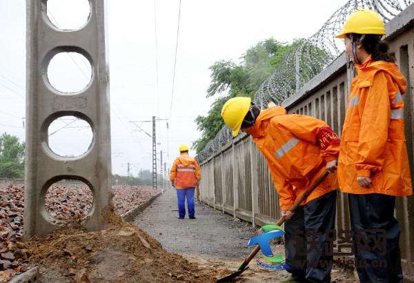图二为:7月22日,郑州供电段职工雨中巡视接触网供电设备,并对新立供电支柱进行培土加固,确保供电安全稳定。.jpg